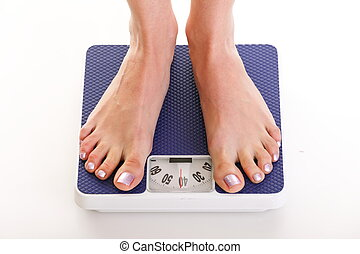 Woman feet and weight scale isolated on white background -...
