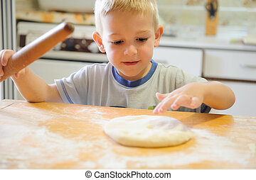 Rolling dough - Little boy rolling dough in the kitchen