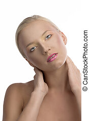 pretty blonde girl with naked shoulders and colored make-up, her head is folded at right, she looks in to the lens with both hands behind the neck