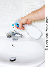 Cleaning bathroom sink with spray bottle