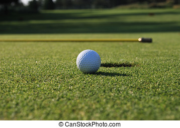 Golf Ball - A golf ball rolling towards the cup - flag on...