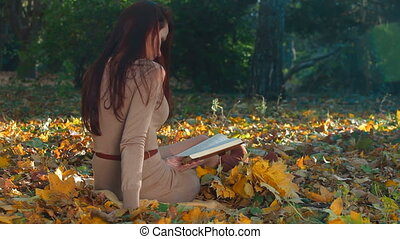 Woman Reading a Book in Autumn Park