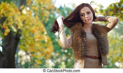 Young Woman Wearing Fur Vest in the Autumn Park, Looking At...