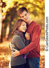 Beautiful couple at autumn park.