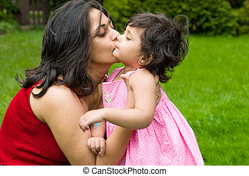 Big Kiss from Mommy - A mother plays kisses her daughter in...