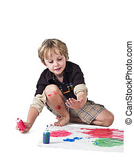 boy doing painting on piece of paper - Boy doing painting on...