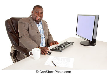 Smiling African American Businessman Sitting at Desk - An...