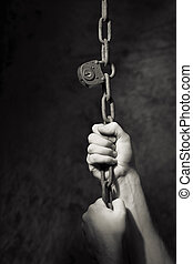 Old Lock and Chain - Monochrome image of hands pulling an...