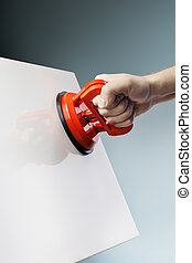 Suction cup tool - Man lifting a white ceramic tile using a...