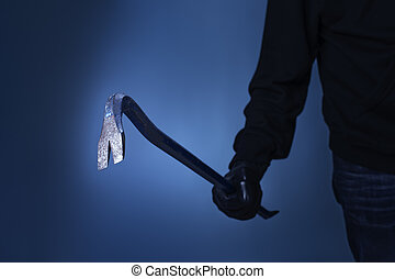 Burglar holding a crowbar in his hand.