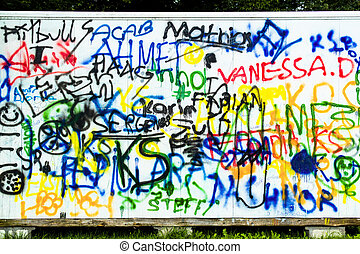 mural and graffiti - many words in colorful paint on a wall