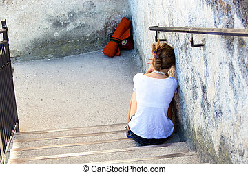 woman sitting on steps - a young woman sitting sad and...