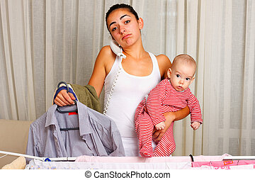 Multi-tasking mother - Young mother doing the laundry,...
