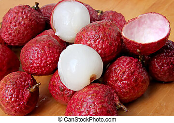 Lychee fruits fresh whole pile unpeeled and peeled