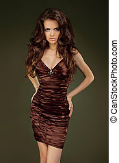 Beautiful woman with curly hair posing in elegant dress. Jewelry and Beauty. Fashion studio photo