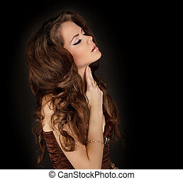 Sensual brunette woman with shiny curly silky hair touching...