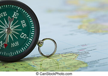 green compass on the map - Cropped image of a green vintage...