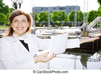 happy architect woman standing in front of a building site