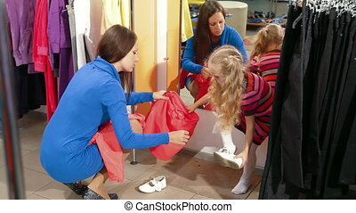 Family Shopping For Girls Clothes - Mother and daughter...