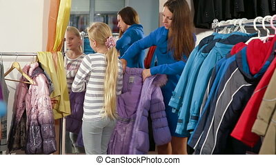 Family Shopping - Mother with two daughters shopping for...