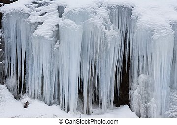 frosty snow storm - Icicles on the side of a rock
