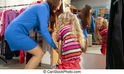 Shopping For Childrens Clothes - Mother and little daughter...