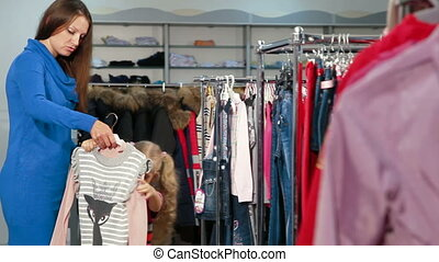 Shopping For Childrens Clothes - Mother and daughter...