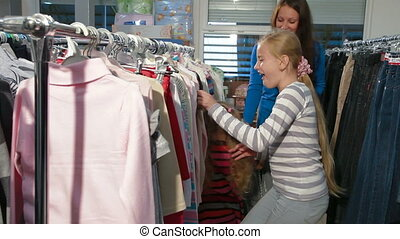 Family Shopping For Clothes - Mother with two daughters...