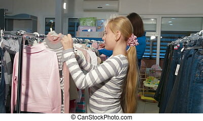 Clothes Shopping - Mother with two daughters shopping for...