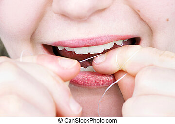 Young woman flossing her teeth - Close up on a young woman...