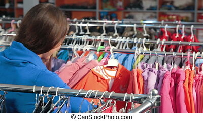 Clothes Shopping - Young woman shopping for clothes in a...
