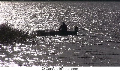 lonely fisherman silhouette in boat and evening light
