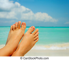 Vacation Concept Womans Bare Feet over Sea background