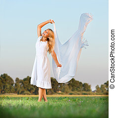 Girl on the Green Field in a White Dress Freedom Concept