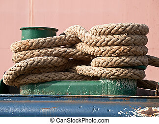 green bollard - green mooring bollard and bundle of rope