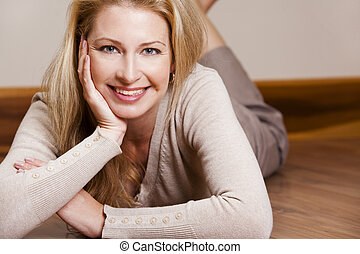 casual woman - pretty blond woman wearing beige top relaxing...