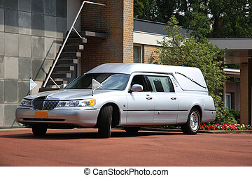 Silver grey hearse parked outside funeral home