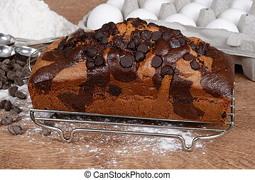 Closeup chocolate chip pound cake with flour and eggs in...