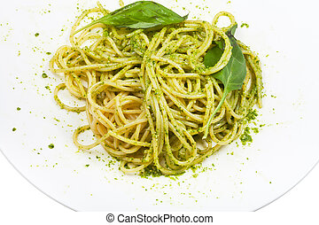 spaghetti mixed with pesto and basil leaf on plate