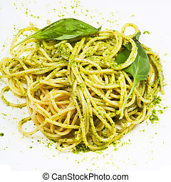spaghetti mixed with pesto and basil leaf