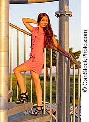 young woman wearing pink dress standing on stairs