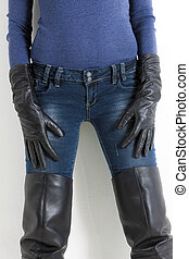 detail of standing woman wearing black boots and jeans
