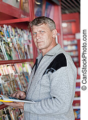 mature man looks the magazine in a bookshop