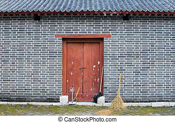 Wall with Broom - A broom leaning against an old wall in...