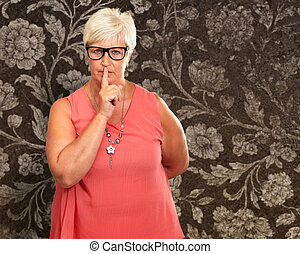 Senior Woman With Finger On Lips