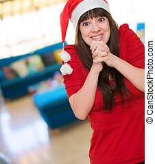 excited woman wearing a christmas hat at her home, indoor