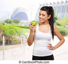 Young woman holding and eating an apple, outdoor