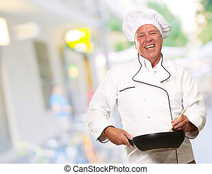 Male Chef Stirring A Non Stick Pan, Background - Portrait Of...