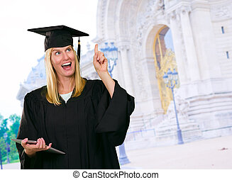 Graduate Woman Holding Digital Tablet standing in front of a...