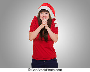excited woman wearing a christmas hat against a grey...